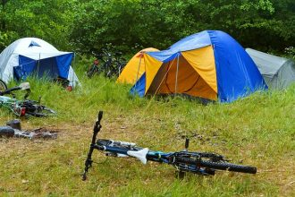 Two tents pitched in a long grass field with bikes on the ground in front of them