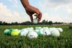 Close up of a lot of golf balls on a patch of grass with a hand reaching down to grab one