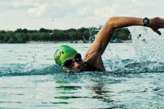 Man swimming in open water, he is wearing a green swimming hat and goggles
