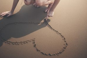 woman crouched down on a beach drawing a heart with her finger in the sand. you can only see her legs and her arms.