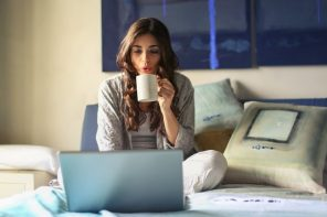 woman sat n front of an open laptop drinkng a cup of coffee and trying to take the stress out of balancing her professional and family life