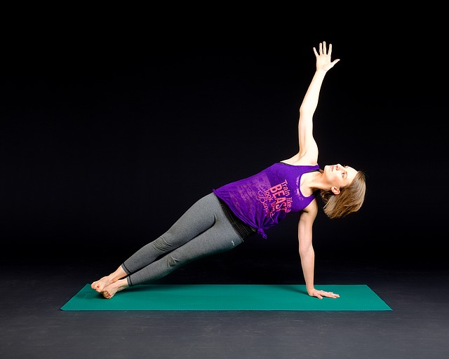woman in workout gear doing a side plank stretch on a green exercise mat set against a plain black background