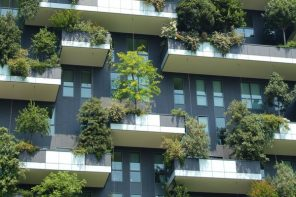 Exterior of a tall building with balconies that are filled with greenery and trees