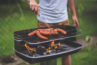 bbq with 6 frankfurter sausages and a man stood turning them over
