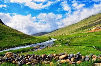beautiful scenery of a stream running between two grassy hills and a beautiful blue sky ditted with white clouds. Nature and the great outdoors at its best.