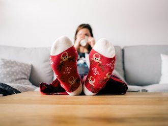 Blurry image of a woman sat on a sifa with her feet up on the table drinkng a cup of teea. her feet are at the front of the photo and they are covered with red reindeer socks.