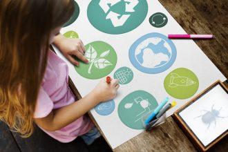 child making a collage of the ways she can help make her home more sustainable and environmentally friendky