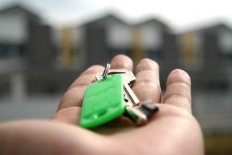 palm of someone's hand holdng a set of house keys on a green keyring in front of a blurry row of houses. It suggests they have just moved and got the keys to their first new home.