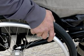 Close up of a mans hand on a wheelchair wheel