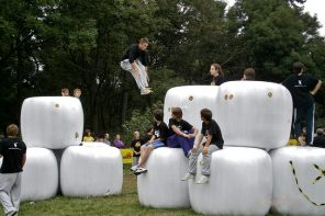 teenagers doing parkour across giant white cubes in a park as an alterantive to playing video games