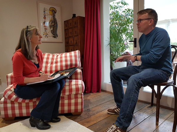 Annabel Boys the Body Stress Release practitioner is say n a red and white checked armchair on the left hand side of the picture. She has a folder on her lap and is askng questions to Simon Stafferton who is sat in a chair on the right. They are in her home studio and there is a pcture of the top half of the human skseleton on the wall.