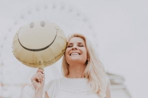 long blonde haired woman with a bright healthy smile holding a yellow smiley face helium balloon with a big wheel in the background