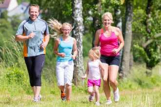 Family of four including blonde mum wearing pink vest and black shorts, dad wearing blue tshirt and long length dark shorts, two blonde haired girls one wearing a light blue vest and white shorts and the other wearing a white vest and pink shorts. they are running together outside in a forest/field area and showing that it is good to get the whole family involved in fitness.