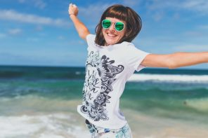 Young woman pictured from the waist up jumping into the air with joy. She is wearng sunglasses and a white t-shirt with print and is on a beack with the sea in the background.