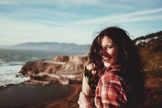 long haired brunette woman in her 40s stood overlooking mountains, she s laughing and looking healthy and care free. She is holdng a small bunch of brown paper wrapped pink roses.