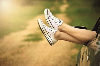 pair of womens feet stickng out of a car window. She ss wearing canvas sneakers and the impression is that she is relaxed and loves life.