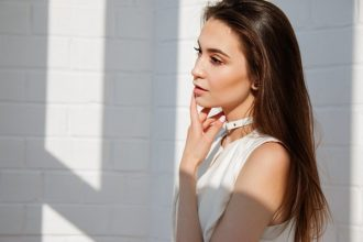 Young brunette female pictured from the chest up. She has long hair that looks healthy and in good condition, because she follows a good natural hair care routine. She is wearng a white sleevless top and is holdng her hand to her mouth. She is stood to the right of the photo against a white brick wall background with shadows.
