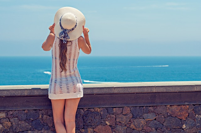 Female wearing a sun hat with a riboon and a white net sun dress that you can see her bikini through. She is stood to the left of the photo in front of a low wall overlooking the sea.