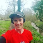 Becky Stafferton from chest up, takng a selfie of herself out running wiith headphones on listenong to music