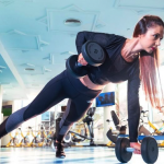 Female in gym doing strength training with dumbells