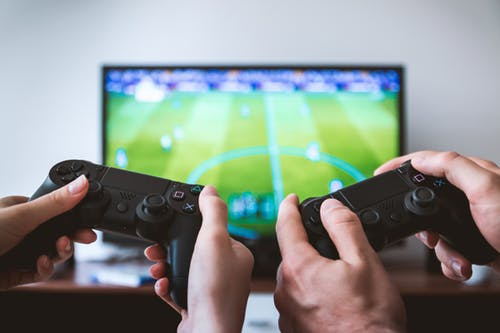 close up of two peoples hands holding game console controllers with a bg TV screen in th background that has a football video game on it.