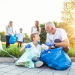 2 women, 1 man and 2 kids outside collecting litter to improve their charity efforts