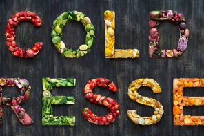 variety of fruts and vegetables laid out on a black background spelling out the words cold pressed