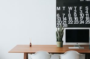 Wooden office desk with two white chairs tucked under. There is a plant on the right hand sde and a reed diffuser on the left sde. On the wall there is half a black weekly calendar