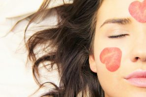 close up of half of a woman's face. Her eyes are closed and her lond brown hair is spread out to the side of her head on a white background. Shae has two red petals in the shape of hearts on her face, one on her cheek and one on her forehead. The images represents the health and wellness trends emerging for women in 2020