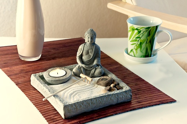 sm,all buddha statue sat in a square tray filled with sand. There is also a tealight candle, some stones and an incense stick. It indicates feng shui in the home