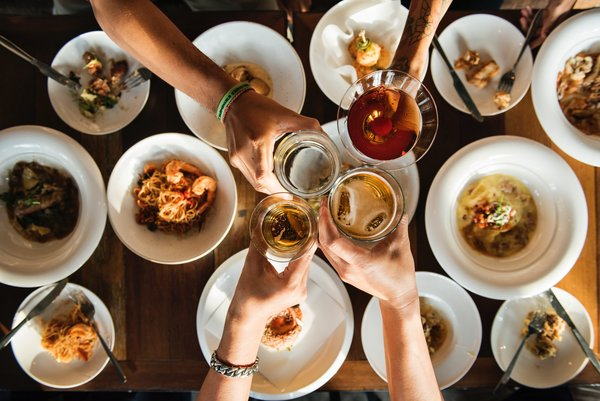 shot from above overlooking a table top of food with four people's arms outstretched touching their drinks glasses together in cheers