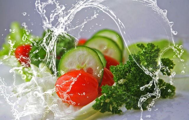 fresh foods ncluding sliced cucumber, tomatoes, lettuce and parsley with a jet iof fresh water leaping over it