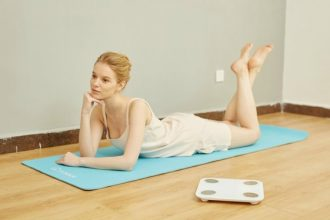 Slim blonde haired female lying on a yoga mat, resting on her elbows and her feet in the air.