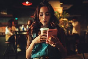 teenage girl holding an iced drink if one hand and a phone in the other. she is looking at the screen fully absorbed in it and not noticing anything else. She is in need of a digital detox.