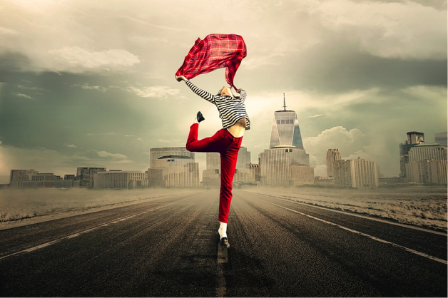 female wearing red troudrs and a stripy long sleveed top, jumping in the air while holding a rd scarf above her head. the background is a cityscape and it is meant to represent her lifestyle choices