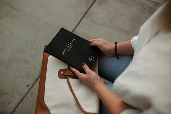 corner shot of a womans hands iin her lap holding a black book as she attempts to find purpose in life.