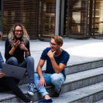 group of three college students sat on outsde steps at fron tof college building. They are laughing together and looking as though they are stress free