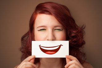 Face of an auburn haired woman holdng a piece of card over her mouth with apicture of a cartoon smile mouth on it