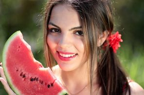 close up of a young brunette female face. She has her hair tied back in a side ponytail fastened with a red flower band and she is holding a slice of watermelon