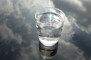 glass of water n a glass background that is reflecting a cloudy sky, suggesting water purification