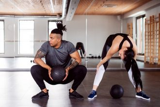 man and woman in a gym dong a HIIT workout together