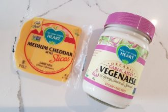 A pack of Follow Your Heart vegan cheese slices next to a jar of Follow Your Heart garlic aioli vegenaise on a white and grey veined marble background