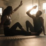 man and woman sat on floor giving each other a high five as they discuss three exercise tips backed by science