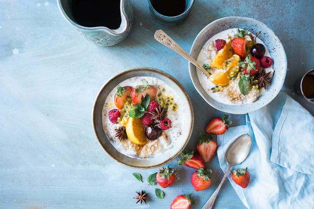 two bowls of oatmeal on a table with strawberries and a spoon scattered around