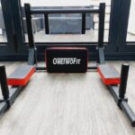 close up picture of the onetwofit wallmounted pull up bar. it is sat on a wooden floor in fron of some glass bi fold doors looking out onto a patio area